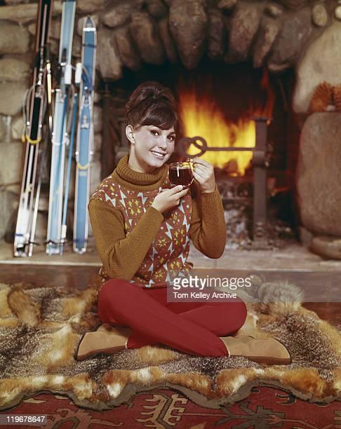 Jeune femme tenant une boisson devant la cheminée, souriant