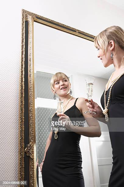 Young woman holding drink looking at reflection in mirror, smiling