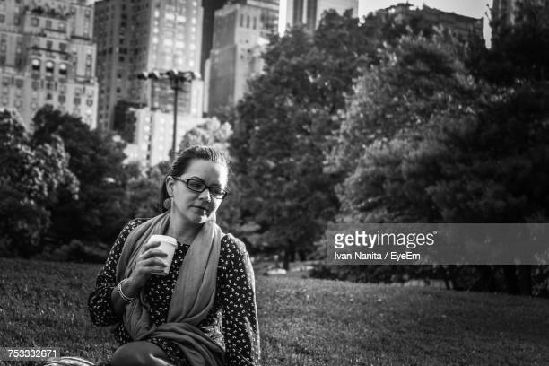 Young Woman Holding Drink While Sitting On Grassy Field At Park