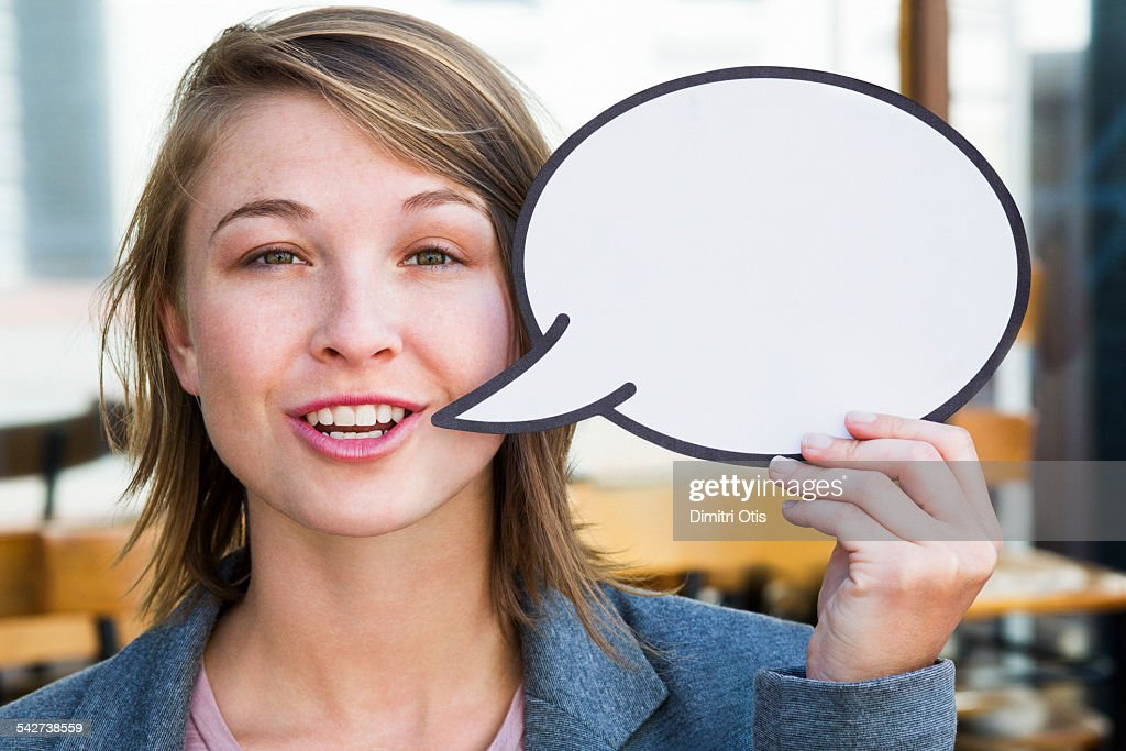 Young woman holding empty speech bubble : Stock Photo