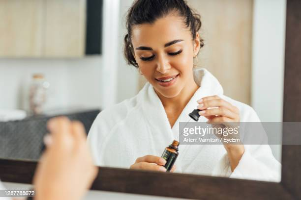 young woman holding essential oil standing in bathroom - essential oil stock pictures, royalty-free photos & images