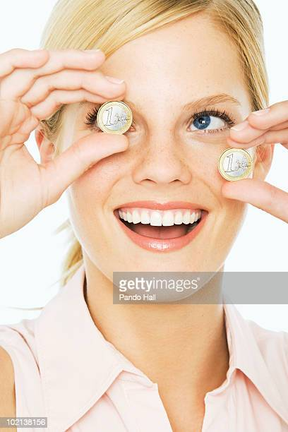 Young woman holding euro coins, laughing, close-up
