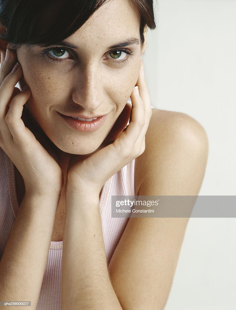 Young woman holding face between hands, close-up : Stockfoto
