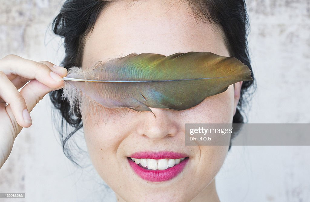 Young woman holding feather over her eyes : Stock Photo
