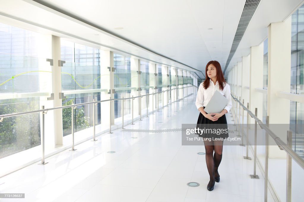 Young Woman Holding File While Walking In Office Corridor : Photo
