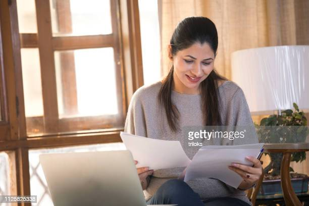 young woman holding financial bill at home - one young woman only stock pictures, royalty-free photos & images