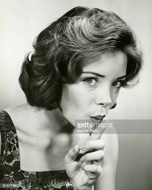Young woman holding finger on lips, posing in studio, (B&W), (Portrait)