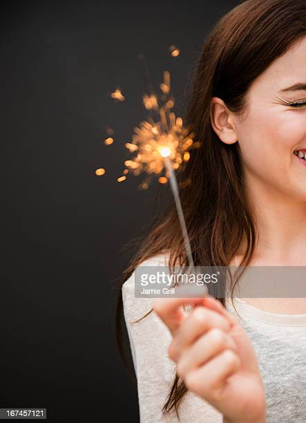 Young woman holding firework