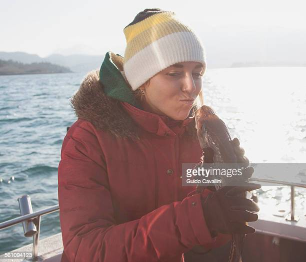 Young woman holding fish on boat