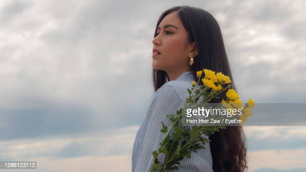 young woman holding flower looking away standing against sky - naypyidaw stock pictures, royalty-free photos & images