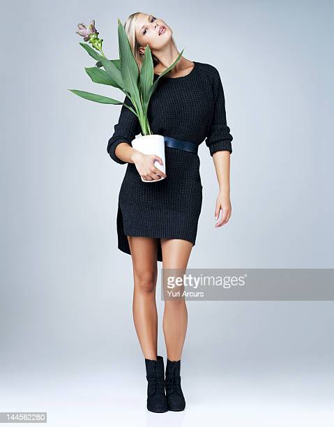 Young woman holding flowering plant, studio shot