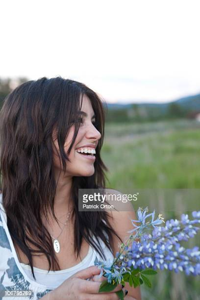 a young woman holding flowers in a green field. - one teenage girl only stock pictures, royalty-free photos & images