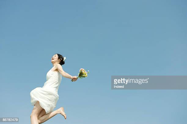 Young woman holding flowers, jumping