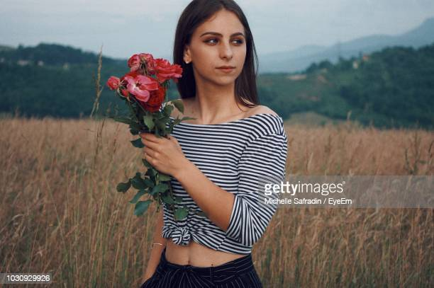 Young Woman Holding Flowers On Field