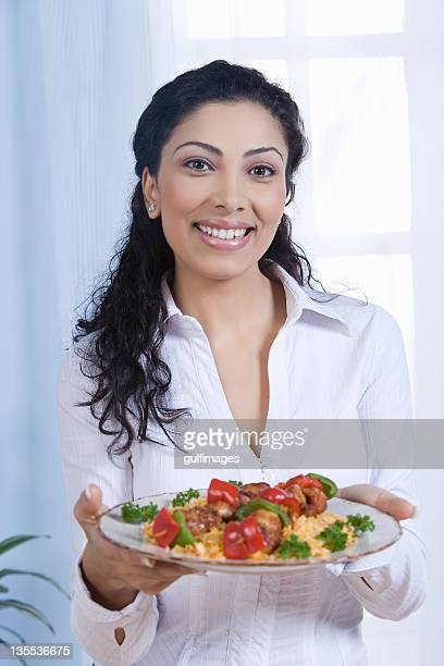 Young woman holding food in plate,portrait