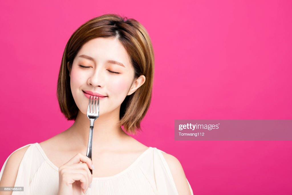 young woman holding fork and enjoy tasty food : Stock Photo