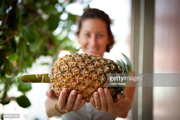 Young woman holding fresh Pineapple