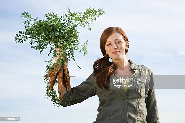 Young woman holding freshly picked carrots