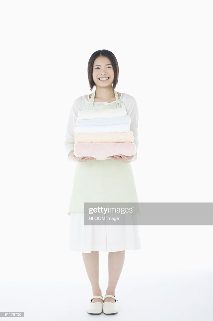 Young woman holding freshly washed towels, studio shot : Stock Photo