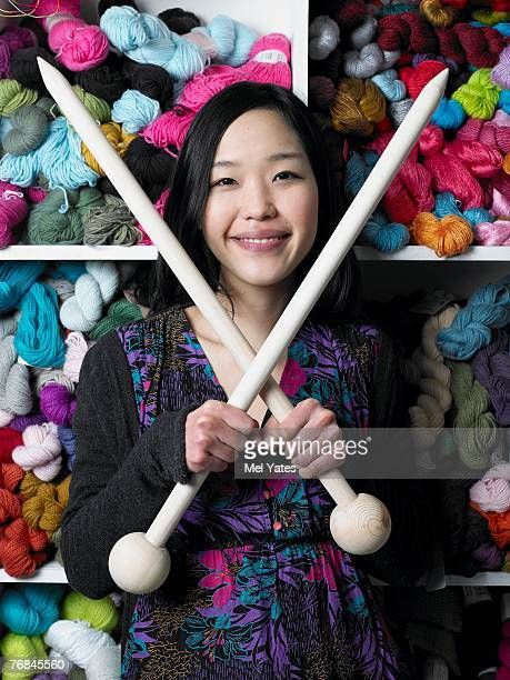 Young woman holding giant knitting needles, smiling, portrait