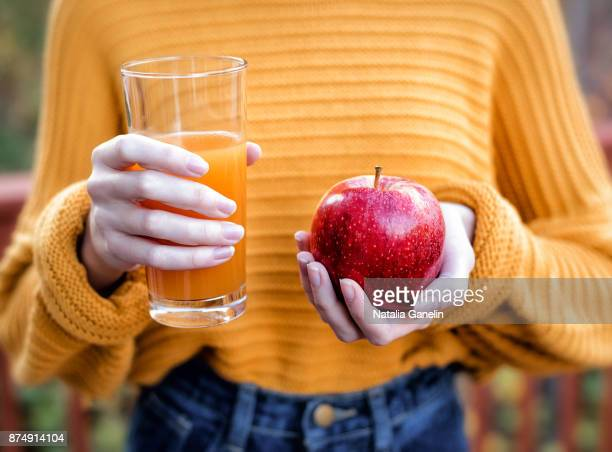 Young woman holding glass of apple juice and fresh apple