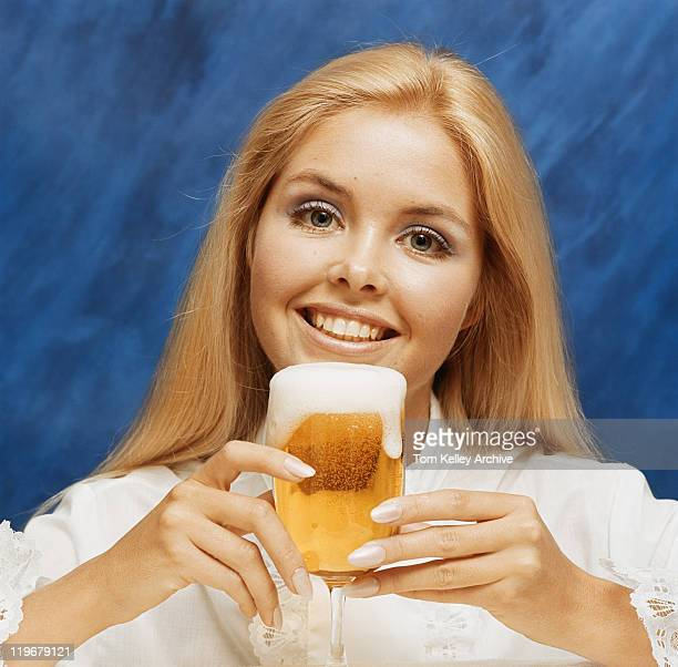 Young woman holding glass of beer, portrait, close-up