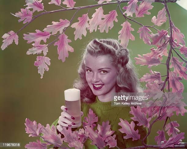 Jeune femme tenant un verre de bière, souriant, portrait