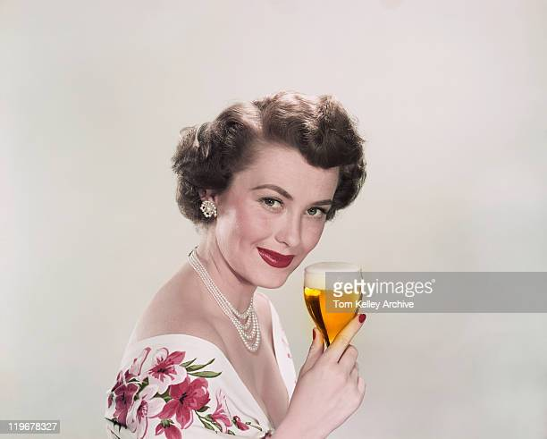 young woman holding glass of beer, smiling, portrait - archiefbeelden stockfoto's en -beelden