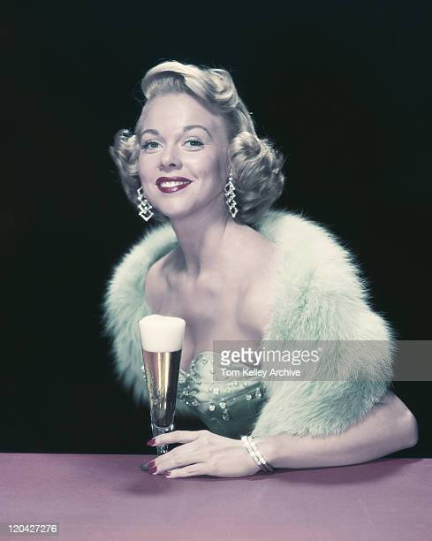 young woman holding glass of beer, smiling, portrait - 1955 stock pictures, royalty-free photos & images