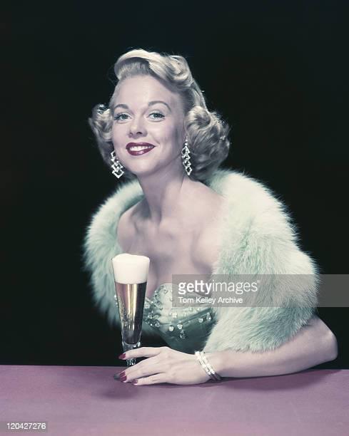Giovane donna con un bicchiere di birra, sorridente, verticale