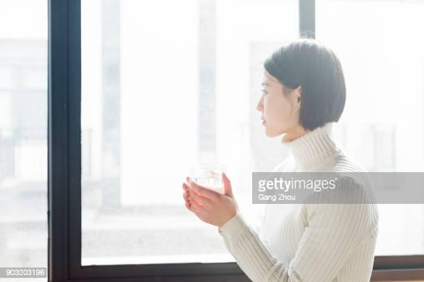ウィンドウを水の入ったグラスを持って若い女性