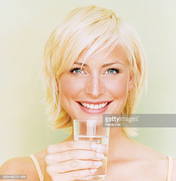 young woman holding glass of water, smiling, close-up, portrait - yeux gris photos et images de collection