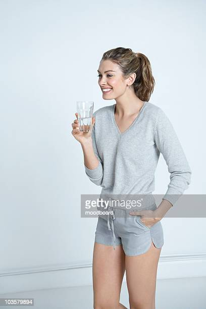 Young woman holding glass of water,  smiling
