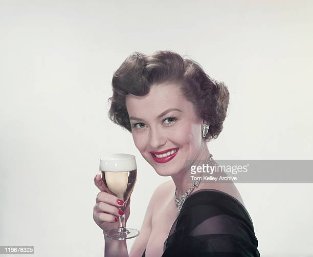 Young woman holding glass of wine, smiling, portrait