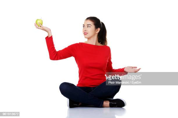 young woman holding granny smith apple while sitting against white background - cross legged stock pictures, royalty-free photos & images