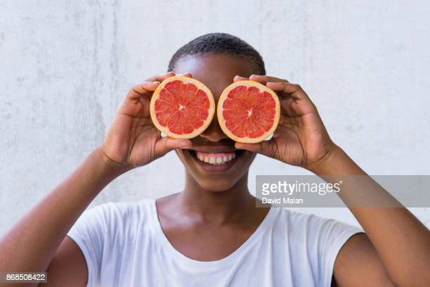 young woman holding grapefruit in front of her eyes. - offbeat stock pictures, royalty-free photos & images