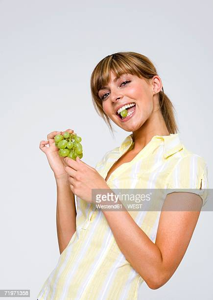 young woman holding grapes between teeth, portrait, close-up - between stock pictures, royalty-free photos & images