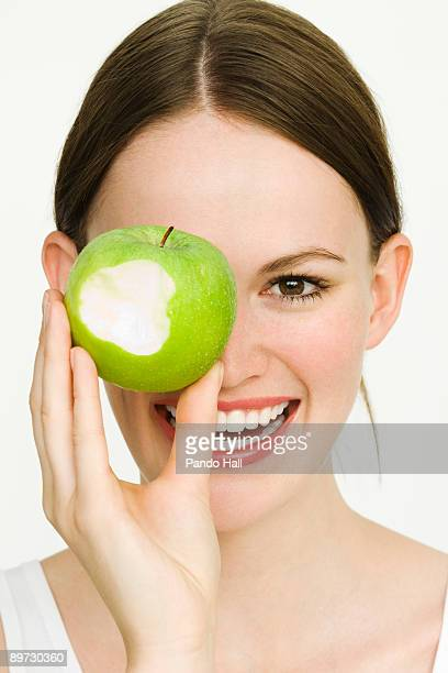 Young woman holding green apple over eye, smiling