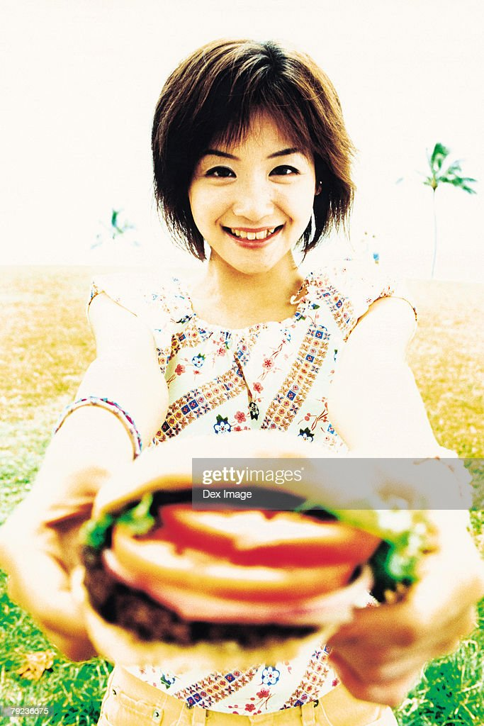 Young woman holding hamburger : Stock Photo