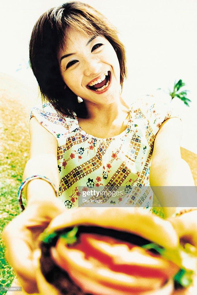 Young woman holding hamburger : Stock Photo