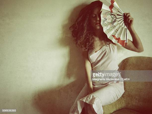 Young Woman Holding Hand Fan While Sitting On Sofa Against Wall