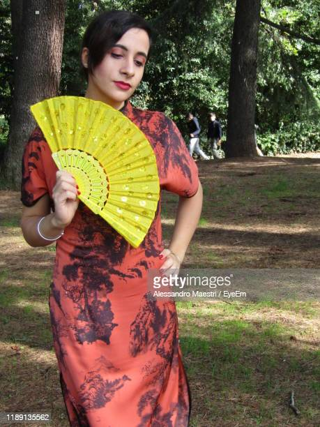 young woman holding hand fan while standing on land - alessandro maestri foto e immagini stock