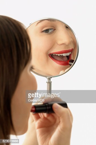 Young Woman Holding Hand Mirror And Applying Lipstick Stock Photo