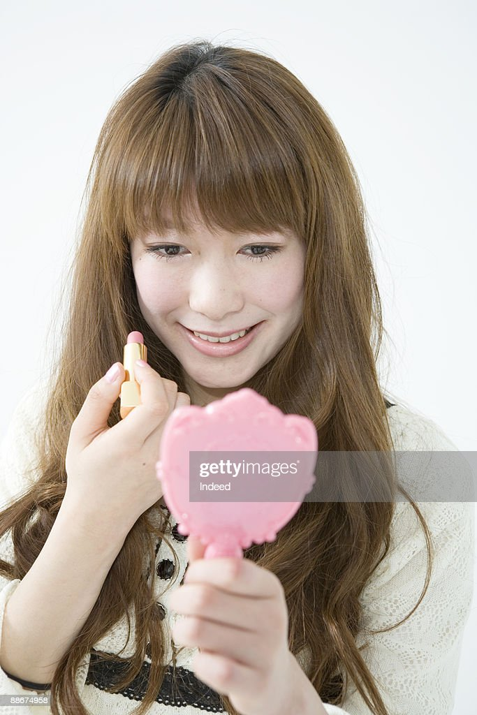 Young Woman Holding Hand Mirror And Lipstick Stock Photo Getty Images