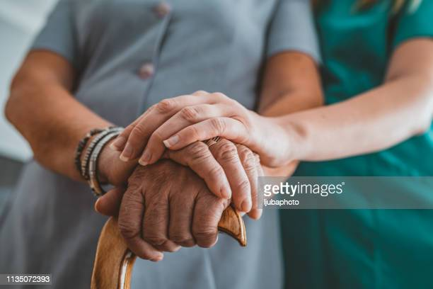 young woman holding hand of old woman with walking stick during the day - walking cane stock pictures, royalty-free photos & images