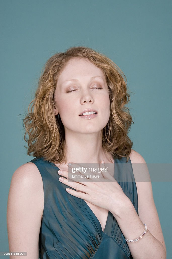 Young woman holding hand to throat, eyes shut : Stock Photo