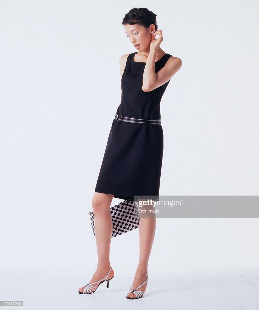 Young woman holding handbag, posing : Stock Photo