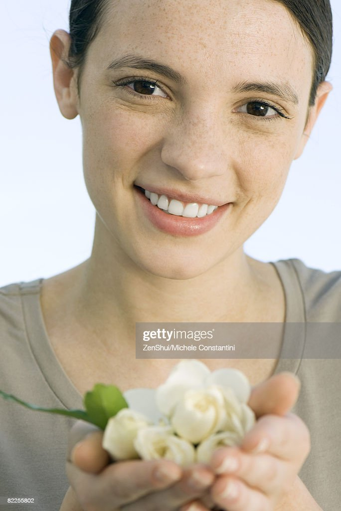 Young woman holding handful of white rose buds : Stock Photo