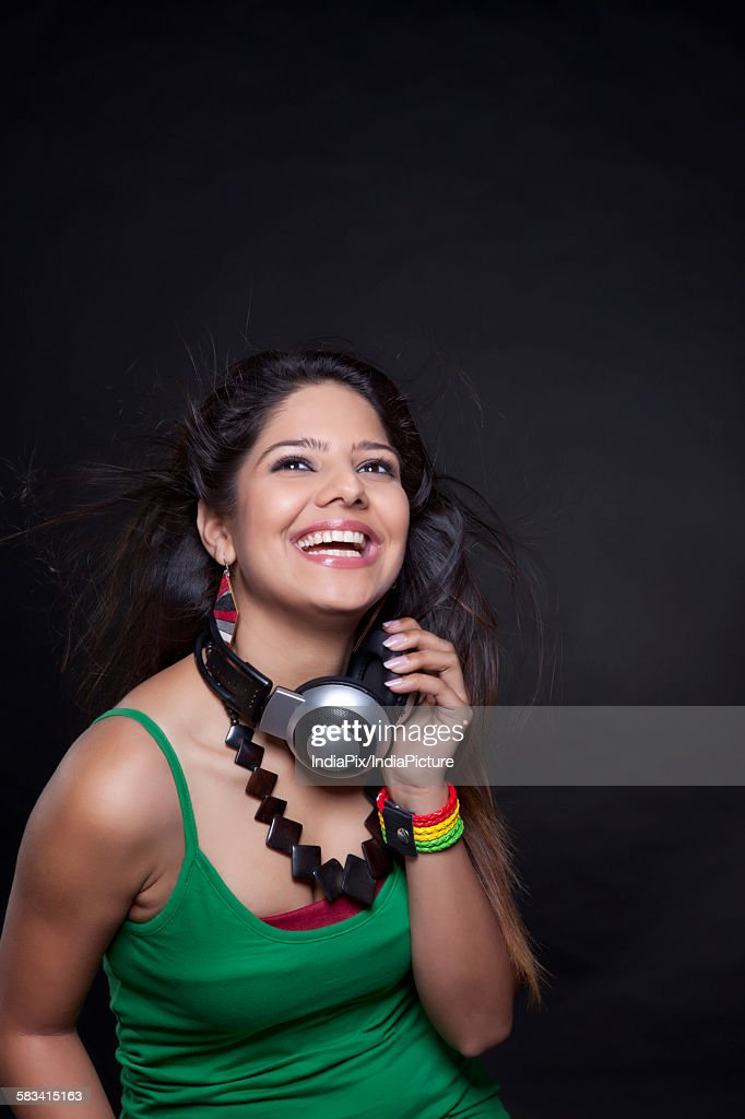 Young woman holding headphones : Stock Photo