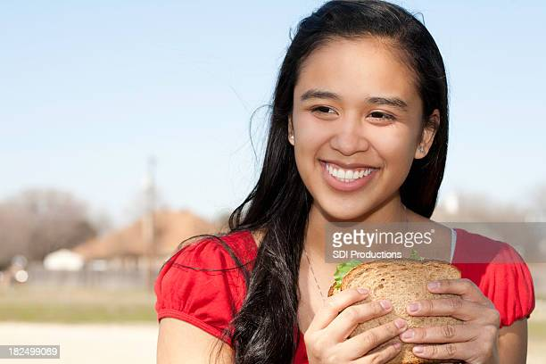 Young Woman Holding Healthy Sandwich at a Park